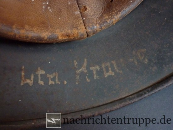 Lieutenants name written onto the neck shield of an M40 steel helmet