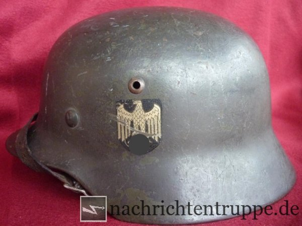 A typical specimen of a steel helmet model M35 - its original green (apple green) was camouflaged but can still be seen
