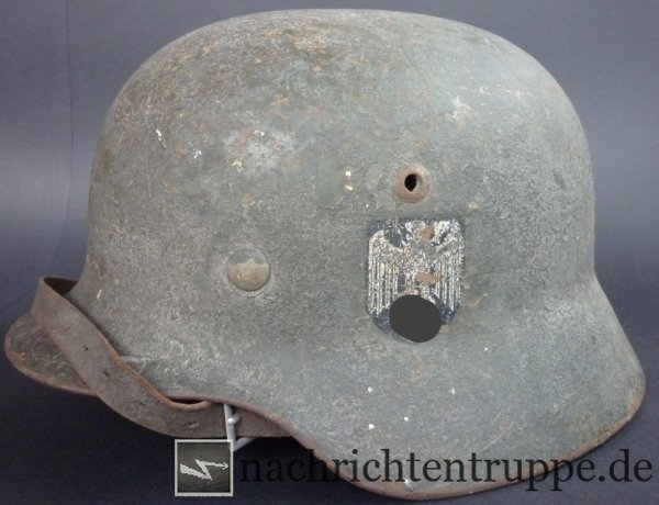 Steel helmet of a soldier at the eastern front line with multiple layers of camouflage painting
